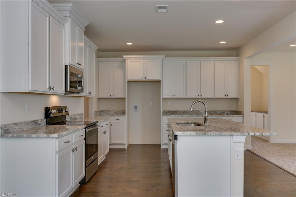 Kitchen includes tons of cabinets and countertop space. Hardwood flooring shown is optional