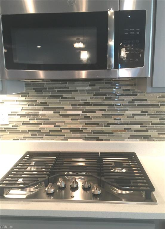 5 burner gas cook top with vented microhood, beautiful glass and stone linear tile backsplash