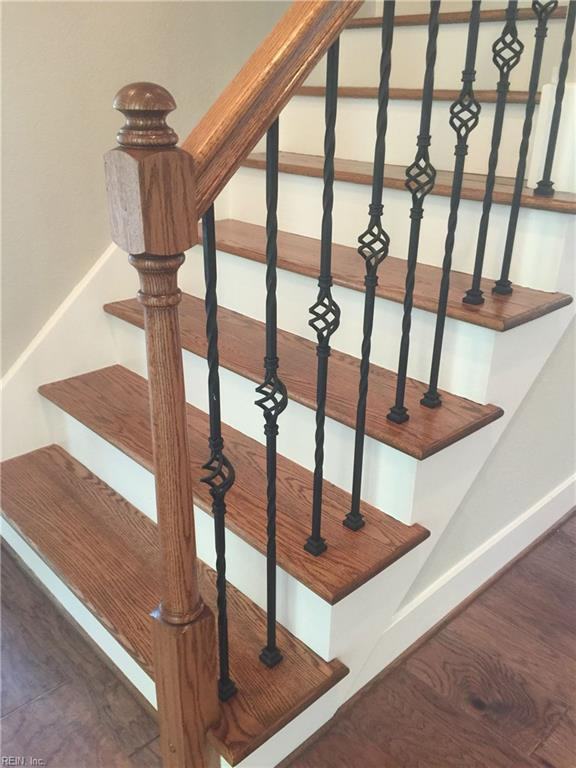 Solid oak treads and decorative wrought iron ballusters lead to a finished 2nd floor.