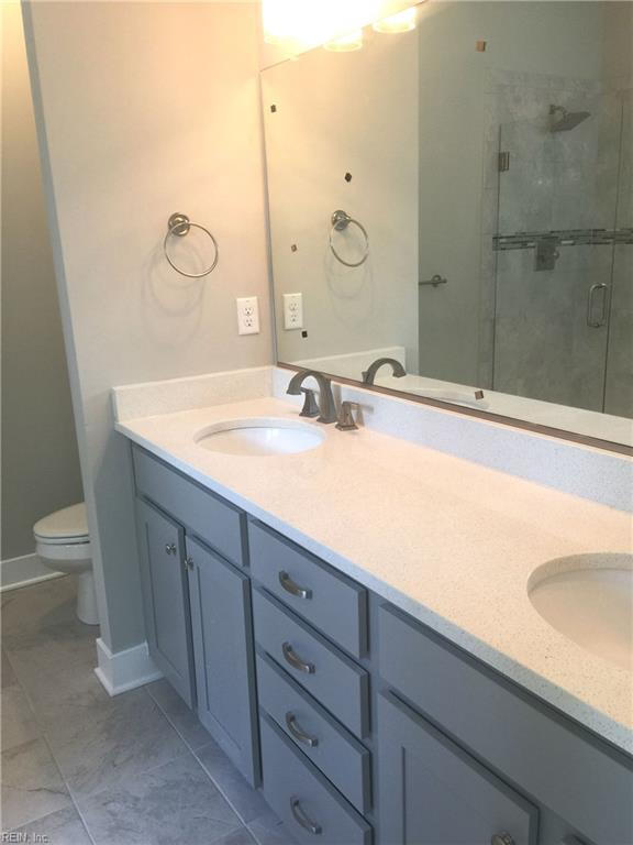 Double bowl vanity with quartz counter top and grey cabinets.
