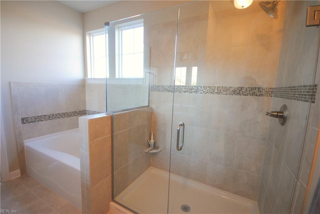 Standard soaking tub with tile surround and optional tile shower with frameless shower door. -  Similar Photo