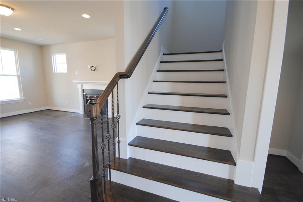 Solid oak tread steps stained to compliment the hardwood floors.  Wrought iron ballusters.