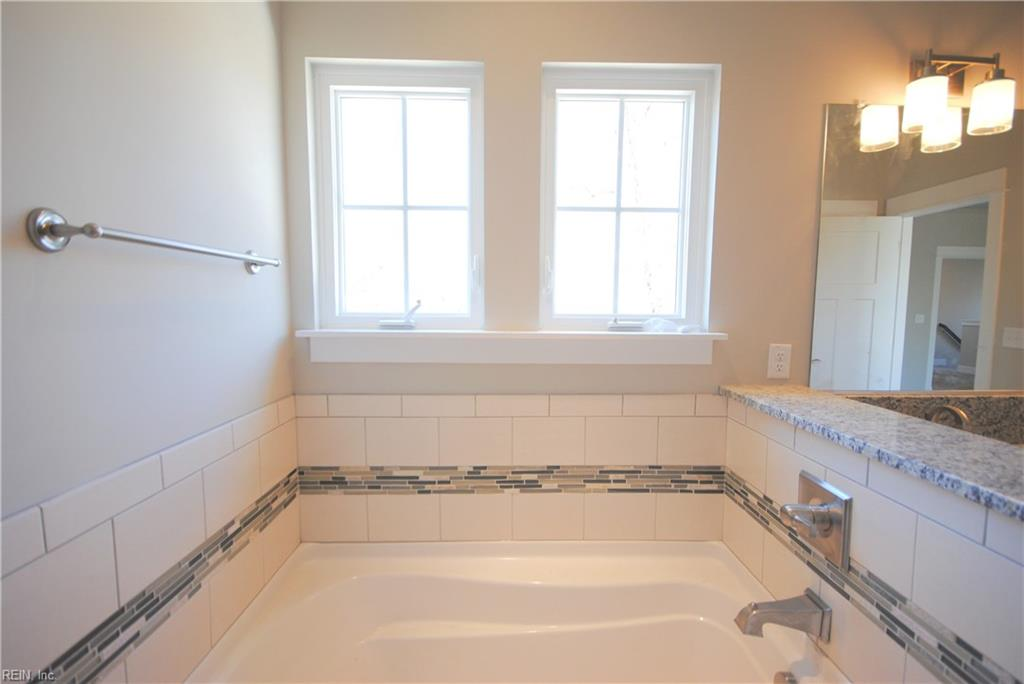 Soaking tub with tile backblash with deco band.  Casement windows above.