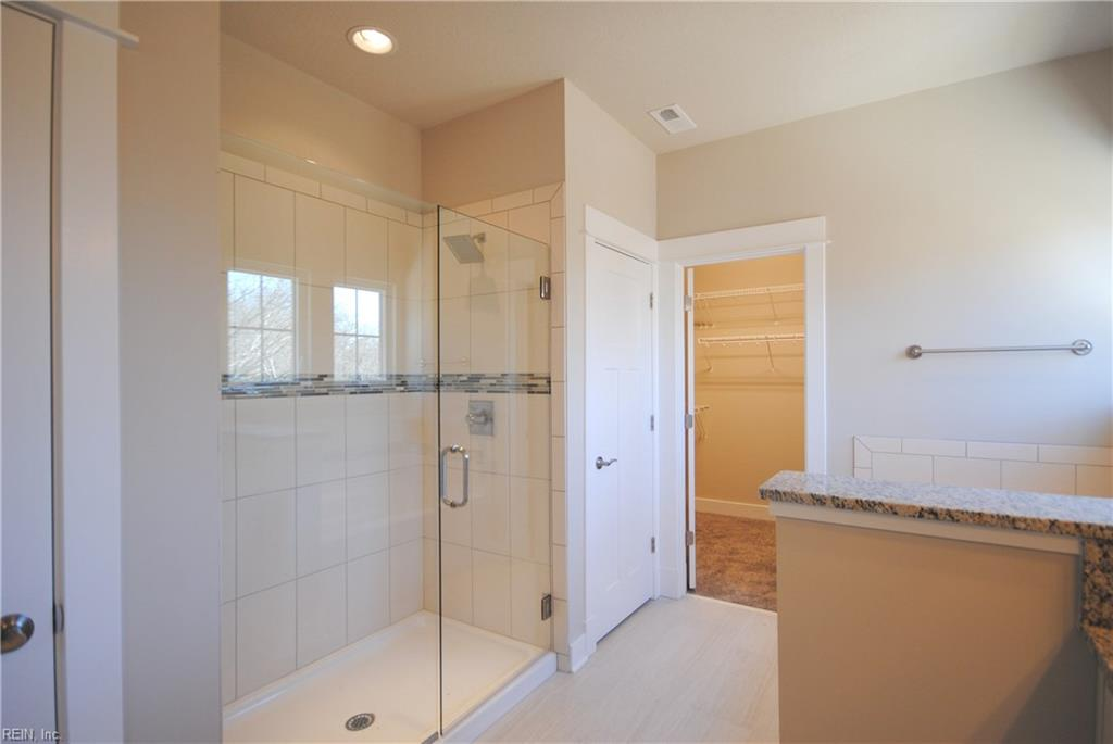 Tile shower with deco band and frameless shower door.