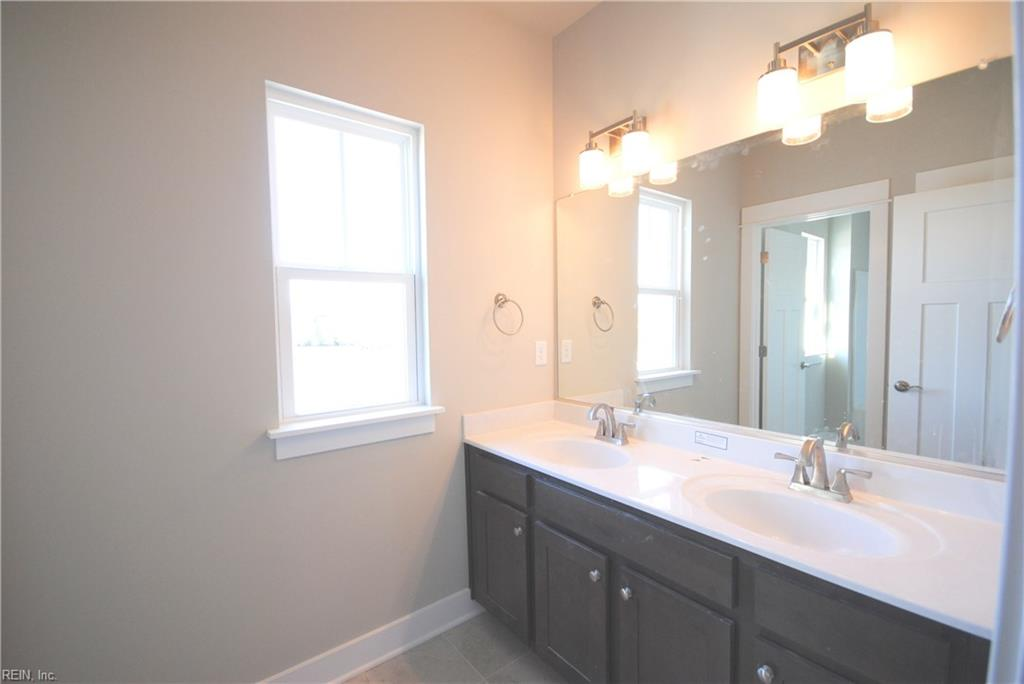 Double vanity in 2nd floor hall bath, separate room for tub/shower and commode.