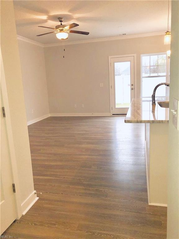 Great Room area to left with kitchen and dining area to right.  Door leads to sodded and fenced backyard Photo shown similar to home being built