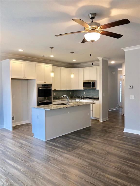 Kitchen includes fully wrapped shaker style cabinets, recessed lighting and pendant lights. Shown with optional gas cooktop and double oven. Photo shown similar to home being built
